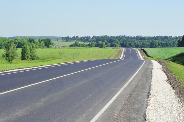 Carretera de asfalto a través del campo verde y cielo azul en día de verano