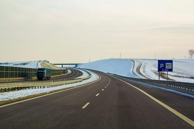 Carretera de asfalto vacía amplia y lisa moderna que se extiende hasta el horizonte bajo un alto puente que gira a la derecha pasando el bosque distante en el día velocidad, viaje confortable y concepto profesional de construcción de carreteras.
