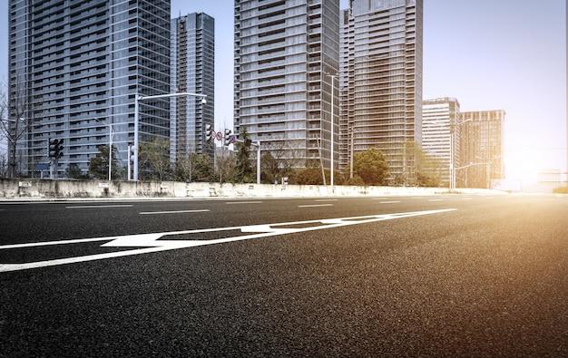 Carretera de asfalto vacía con edificios de fondo