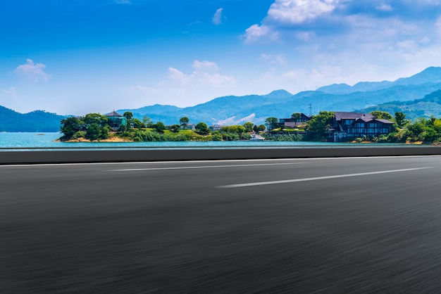 Carretera de asfalto vacía y paisaje natural bajo el cielo azul