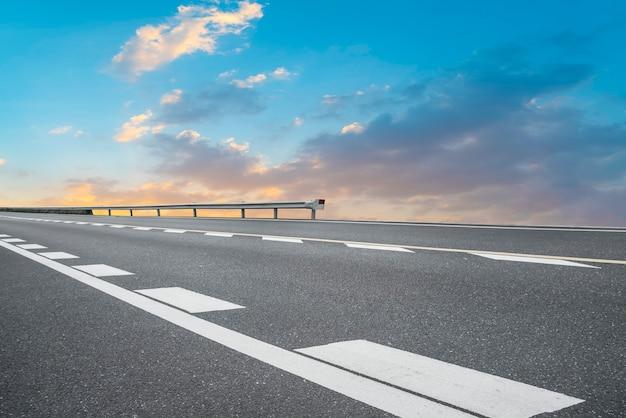 Carretera de asfalto vacía y paisaje natural en la puesta de sol