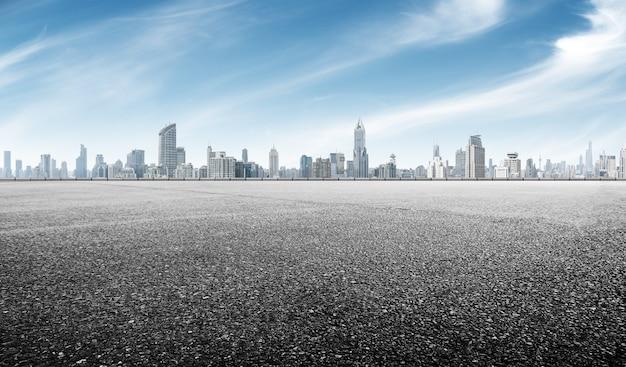 Carretera de asfalto vacía con paisaje urbano de shanghai en cielo azul