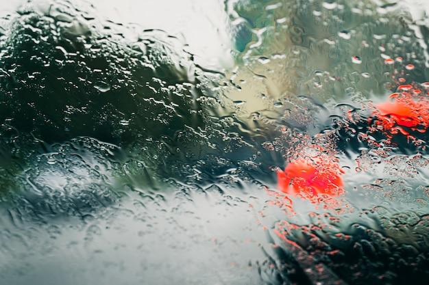 Carretera de la ciudad vista a través de gotas de lluvia en el parabrisas del coche