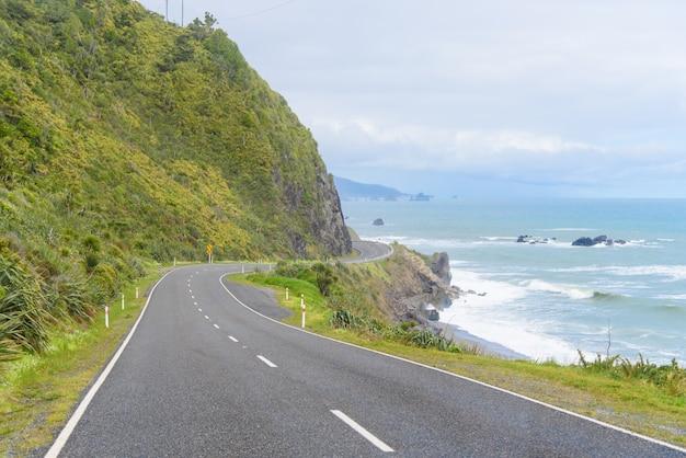 Carretera costera de nueva zelanda: un camino escénico serpentea a lo largo de la costa occidental de la isla sur de nueva zelanda.
