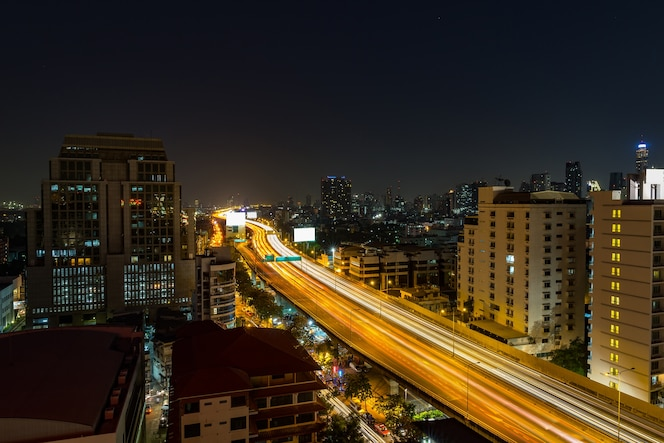 Carretera de tráfico urbano de noche con paisaje urbano en la ciudad moderna