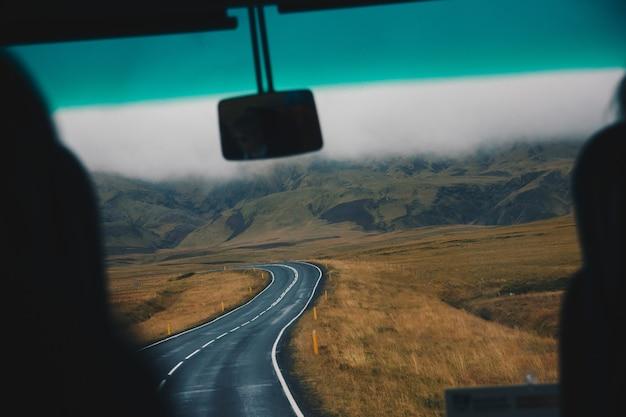 Carretera estrecha en un hermoso gran campo de tiro desde el interior del automóvil