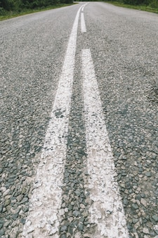 Carretera de gravilla de asfalto minúsculo, camino asfaltado en bruto de piedras granulares con marcas blancas en perspectiva