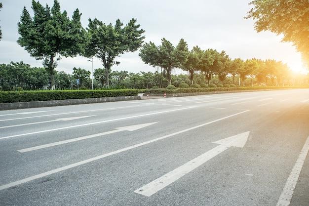 Carretera de hormigón con flechas al amanecer