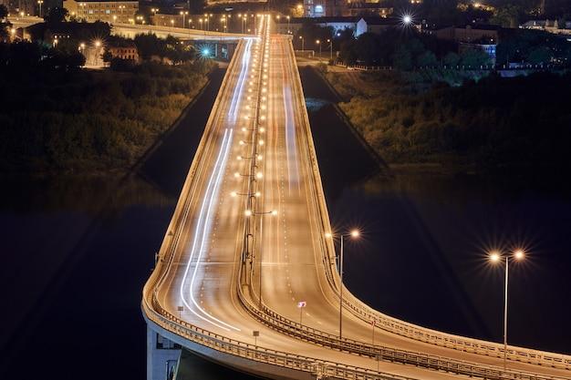 Carretera en las luces de la noche. senderos, vetas y senderos de luz de coche rápido en el camino del puente de intercambio. rayas de pintura de luz nocturna