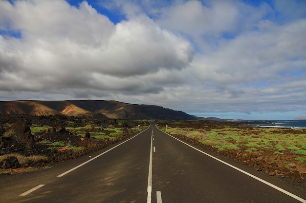 Carretera en medio de un campo de hierba con una montaña en la distancia bajo un cielo nublado