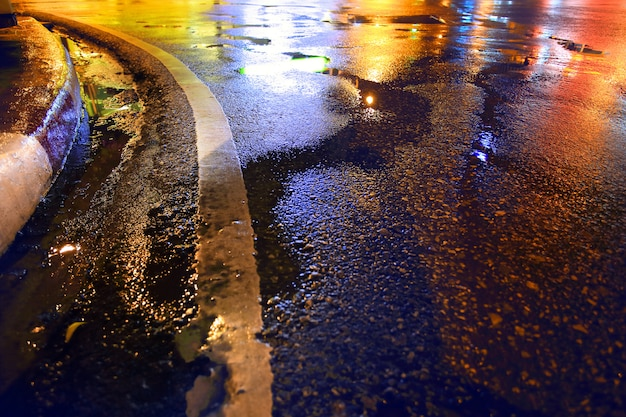 Carretera mojada, noche lluviosa en la ciudad.