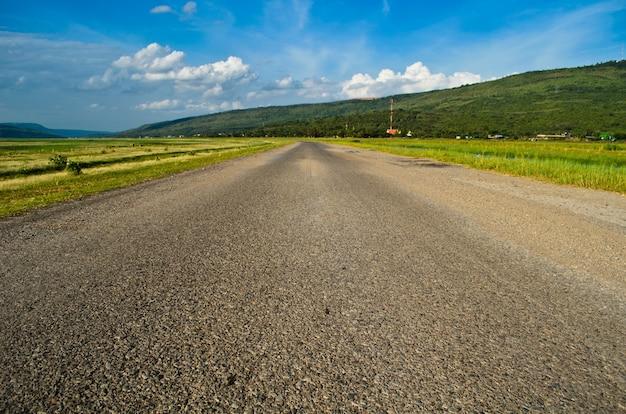 Carretera nacional hermosa y cielo azul entre el campo rural.