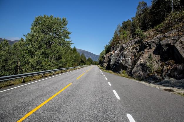 Carretera en noruega sobre montañas, colinas y fiordos.