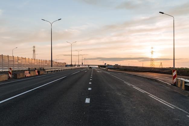 Carretera de nueva construcción con paneles insonorizados con el telón de fondo de la puesta de sol