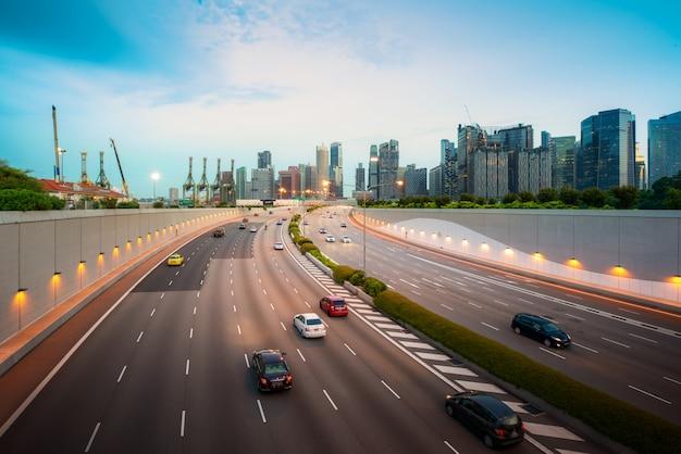 Carretera ocupada y fondo de la ciudad durante la hora pico con vehículo borroso en movimiento