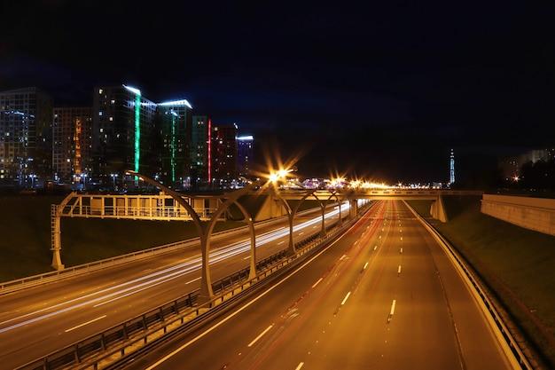 Carretera de paisaje urbano nocturno con senderos de luz de coches