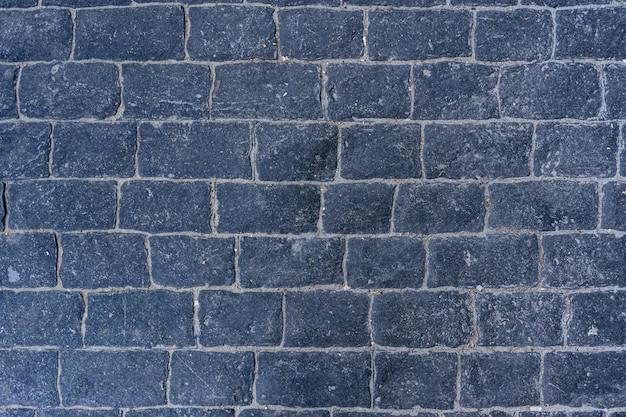Carretera pavimentada de adoquines con cursos de borde en la textura de la acera