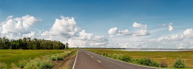 Carretera pavimentada local con pastizales en escena rural sobre fondo de cielo azul