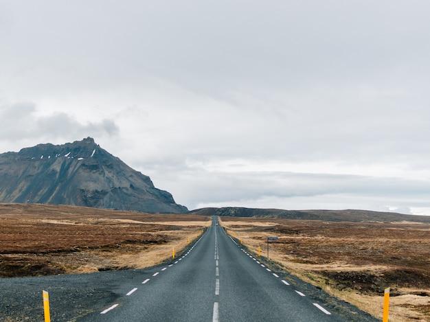 Carretera rodeada de colinas cubiertas de vegetación y nieve bajo un cielo nublado en islandia