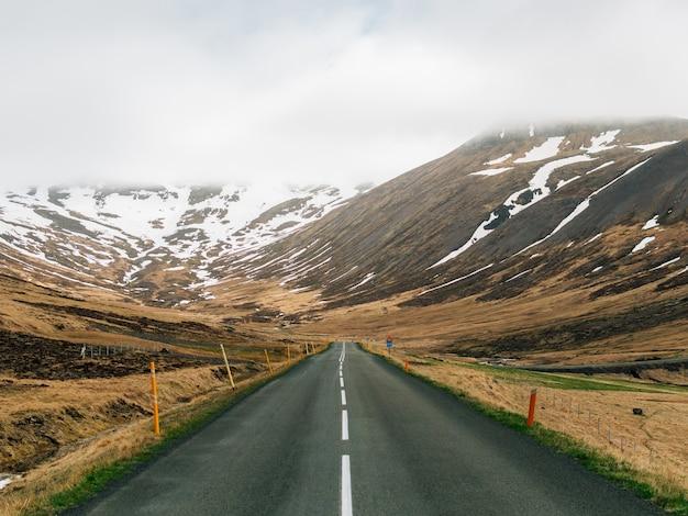 Carretera rodeada de colinas cubiertas de vegetación, nieve y niebla en islandia