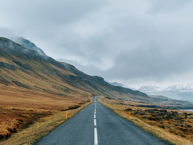 Carretera rodeada de rocas cubiertas de vegetación y nieve bajo un cielo nublado y niebla