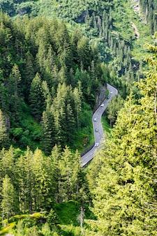 Carretera serpenteante a través de los alpes suizos con coches antiguos