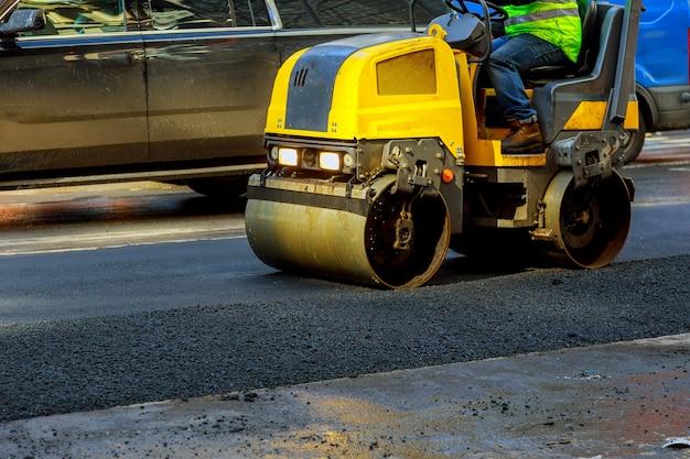Carretera urbana en construcción, asfaltada de rodillo amarillo.
