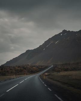 Carretera vacía con curvas junto a una hermosa montaña rocosa bajo un cielo gris y sombrío