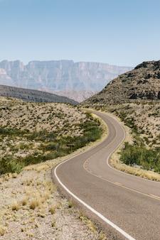 Carretera vacía en medio de un campo seco con arbustos y montañas en la distancia