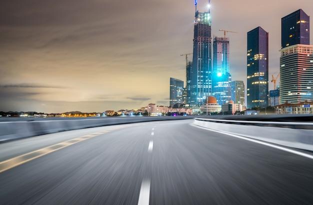 Carretera vacía con paisaje urbano y horizonte de qingdao, china.