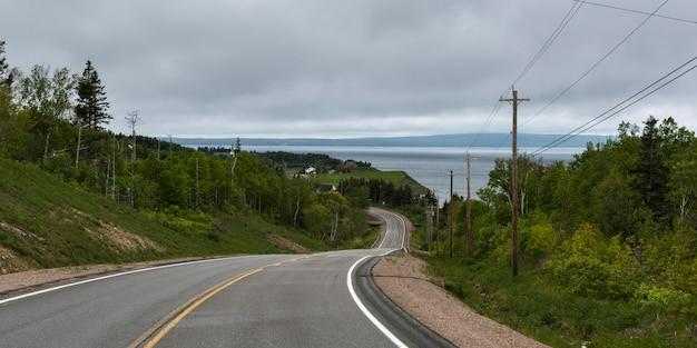 Carretera vacía que pasa a través del paisaje rural, grand river, isla cape breton, nueva escocia, canadá