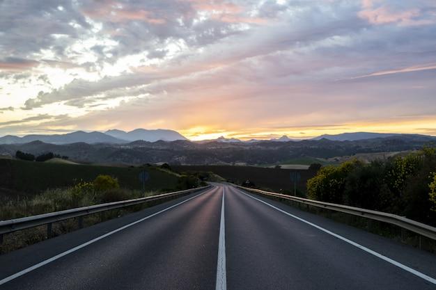 Carretera vacía rodeada de colinas bajo el cielo nublado del atardecer