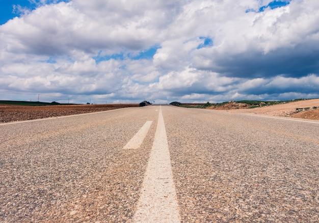 Carretera vacía rodeada de colinas bajo un hermoso cielo nublado
