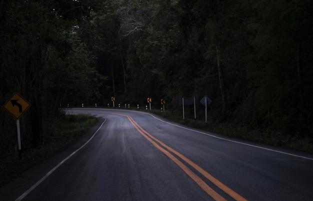 Carretera en la vista oscura en la carretera de montaña entre árboles forestales verdes - carretera asfaltada curva solitaria de miedo por la noche