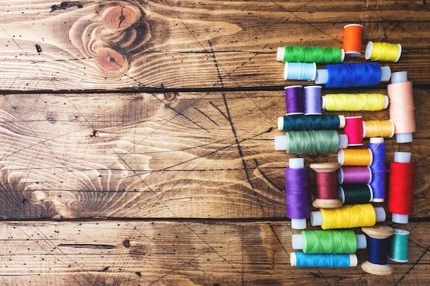Carretes coloreados del hilo presentados en filas en fondo de madera. copia espacio