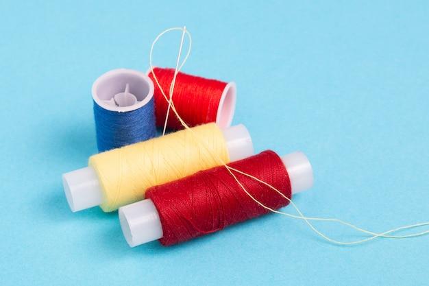 Carretes de hilo de coser de colores sobre un fondo azul.