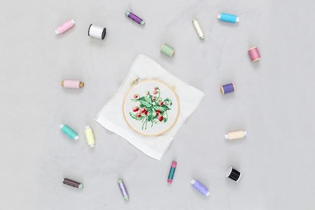 Carretes en hilos de colores y bordados de flores.