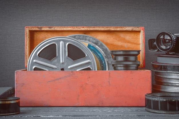 Carretes con películas en una caja de madera, lente y una vieja cámara de cine.