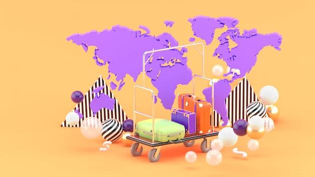 Carretilla de botones entre el mapa mundial y bolas de colores en la naranja. representación 3d