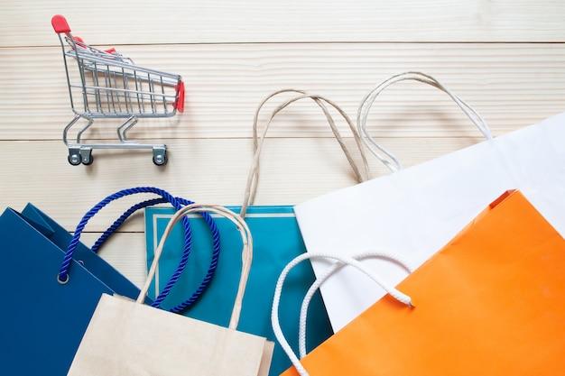 Carretilla de las compras y bolsos de compras multicolores en fondo de madera