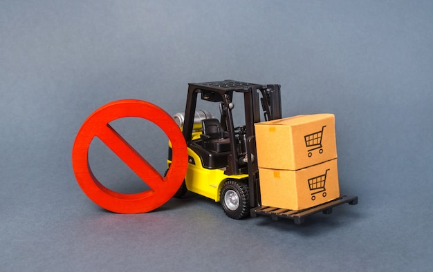 La carretilla elevadora amarilla lleva boxex y un símbolo de prohibición rojo no. guerras comerciales de embargo