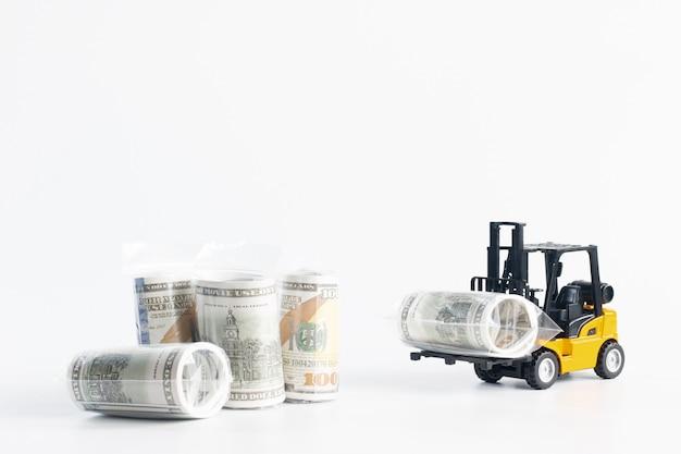 Carretilla elevadora en miniatura cargando billete de un dólar envuelto en plástico aislado en blanco, financiero