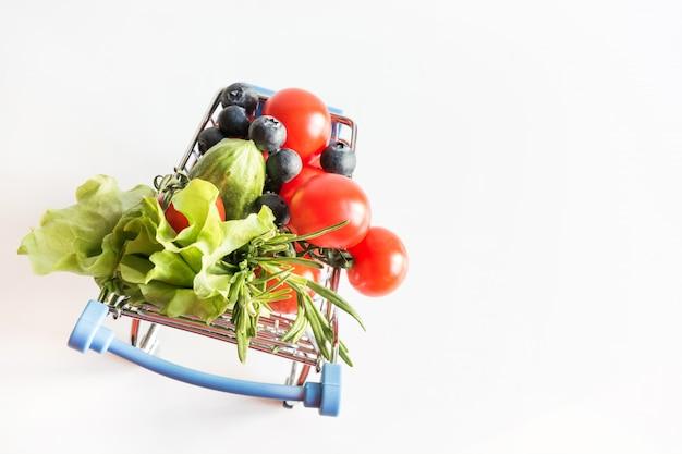 Carretilla de la tienda de comestibles con los tomates en azul.
