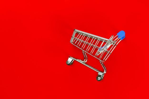 Carretilla vacía para compras de productos en el supermercado sobre fondo rojo.