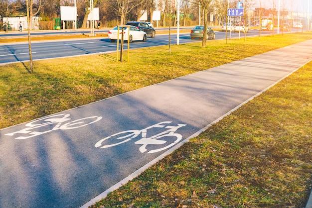 Carril bici vacía de asfalto en la ciudad con hierba verde