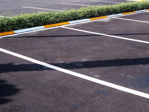 Carril de estacionamiento en camino de concreto, estacionamiento de automóviles vacío.