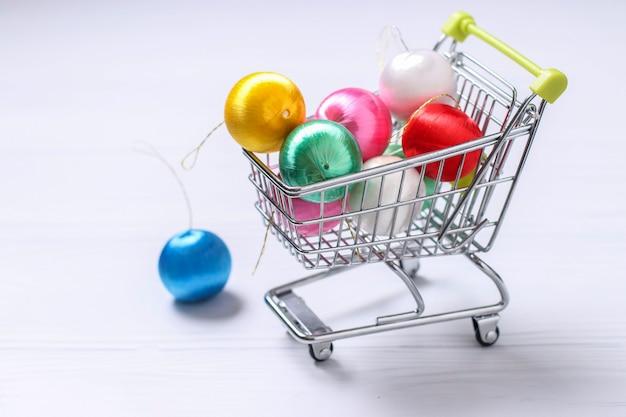 Carrito y coloridas bolas de año nuevo sobre fondo blanco, compras laicas planas creativas, orientación horizontal, espacio de copia