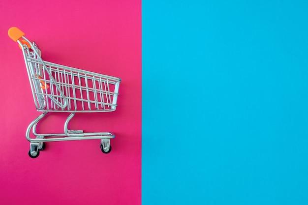 Carrito de la compra de autoservicio de supermercado con fondo rosa y azul.