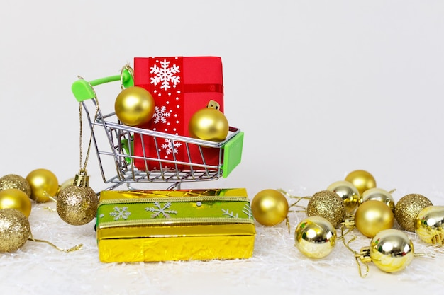 Carrito de la compra con cajas de regalo y esferas doradas sobre un copo de nieve sobre un fondo blanco.