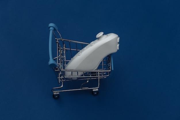 Carrito de la compra con joystick moderno sobre fondo azul clásico. color 2020. vista superior